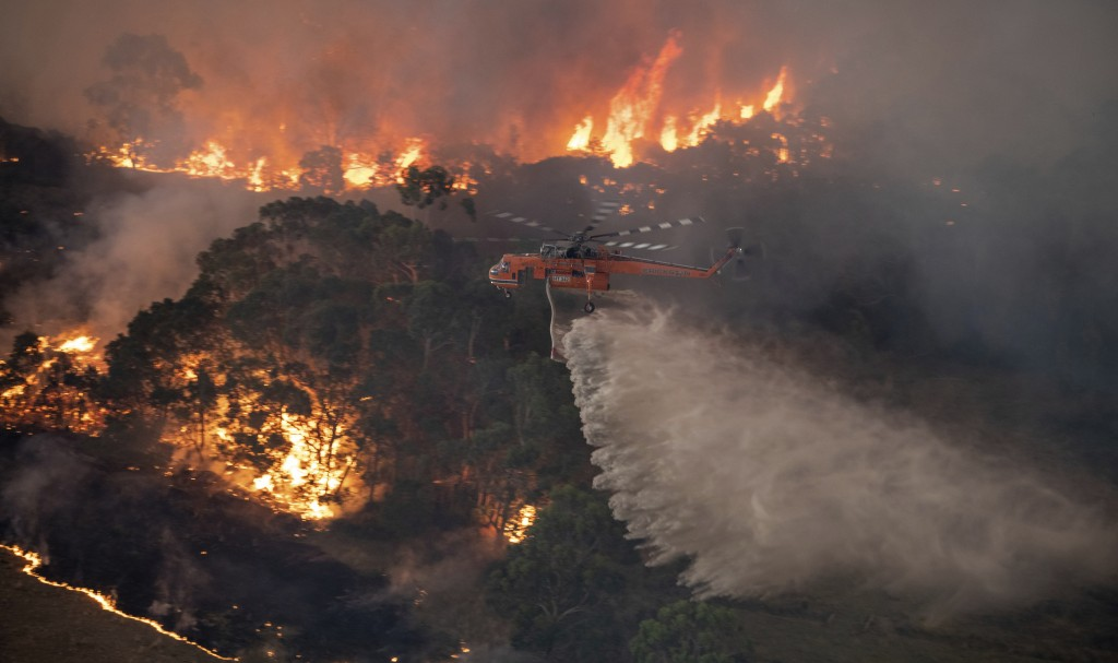 In this Monday, Dec. 30, 2019 photo provided by State Government of Victoria, a helicopter tackles a wildfire in East Gippsland, Victoria state, Austr...