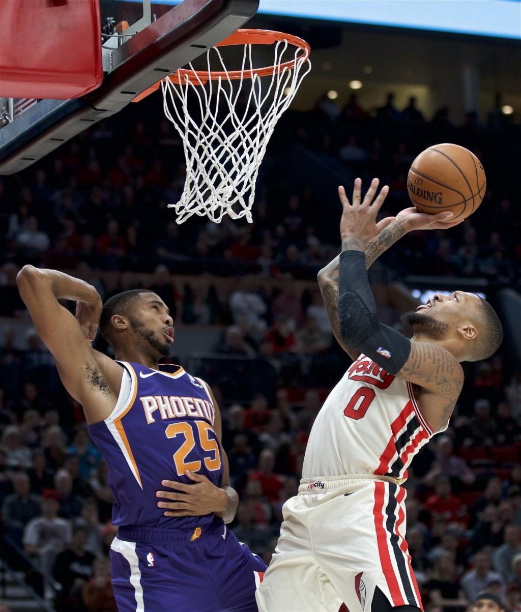 Portland Trail Blazers guard Damian Lillard, right, shoots over Phoenix Suns forward Mikal Bridges during the second half of an NBA basketball game in...