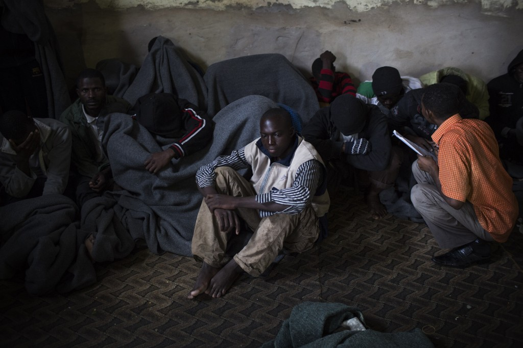FILE - In this Nov. 29, 2013 file photo, migrants cover themselves with blankets in a detention center in the Abu Salim district on the outskirts of T...