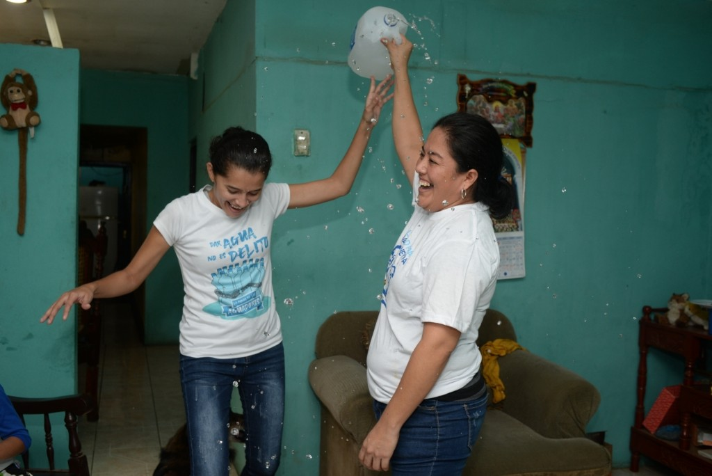 Ivania Alvarez holds up an open jug of water to celebrates with Neyma Hernandez after their release from prison, at her home in Managua, Nicaragua, Mo...