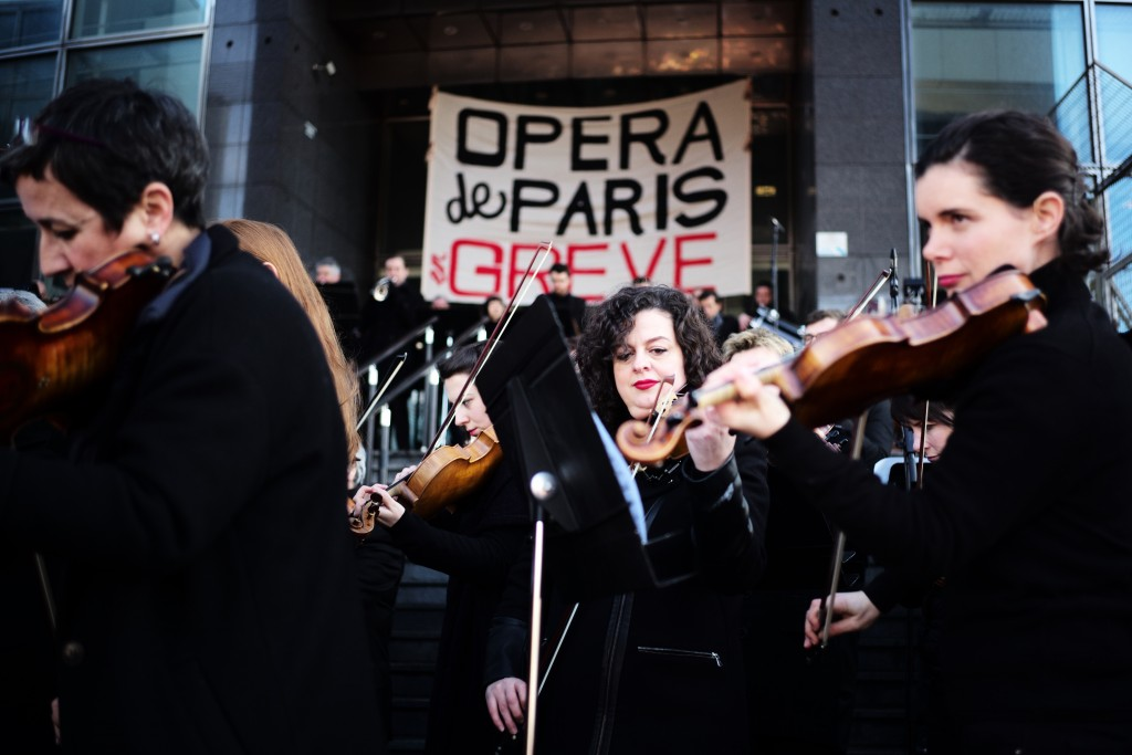Striking musicians of the Paris Opera house perform outside the Bastille Opera house Tuesday, Dec. 31, 2019 in Paris. Banner reads : Paris Opera on st...