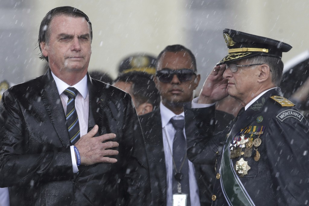FILE - In this April 17, 2019 file photo, Brazil's President Jair Bolsonaro puts his hand over his heart as Army Commander Edson Leal Pujol salutes du...