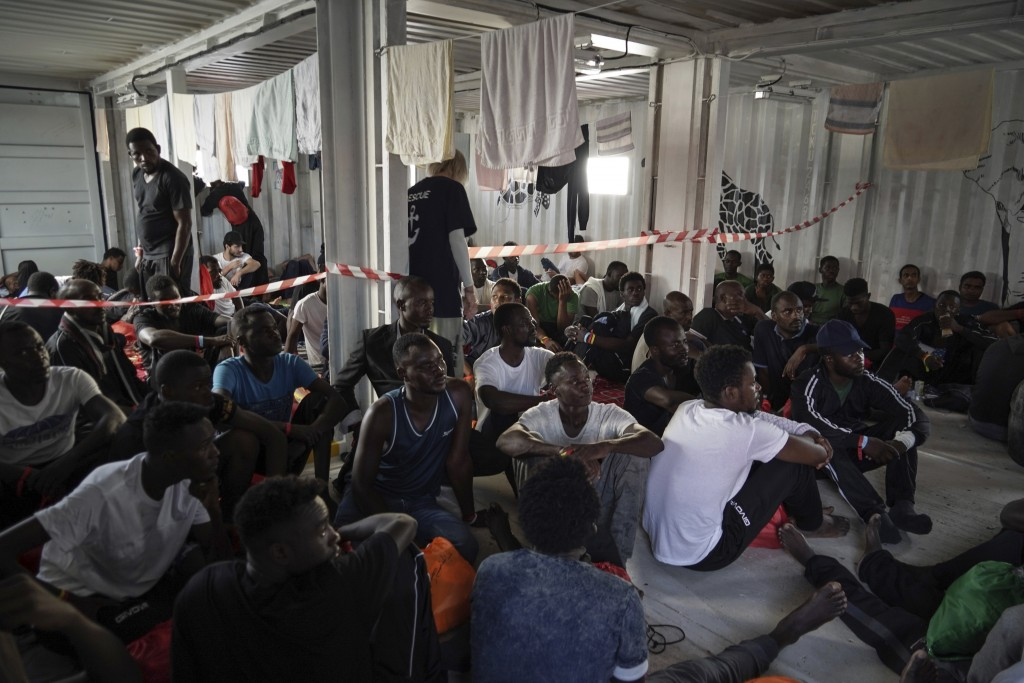 In this Sept. 18, 2019 photo, migrants rescued at sea rest in the men's shelter aboard the Ocean Viking humanitarian ship as it sails in the Mediterra...
