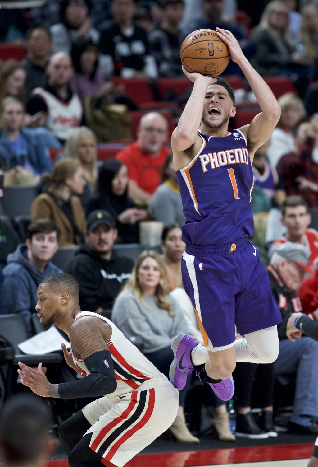 Phoenix Suns guard Devin Booker, right, shoots over Portland Trail Blazers guard Damian Lillard during the second half of an NBA basketball game in Po...