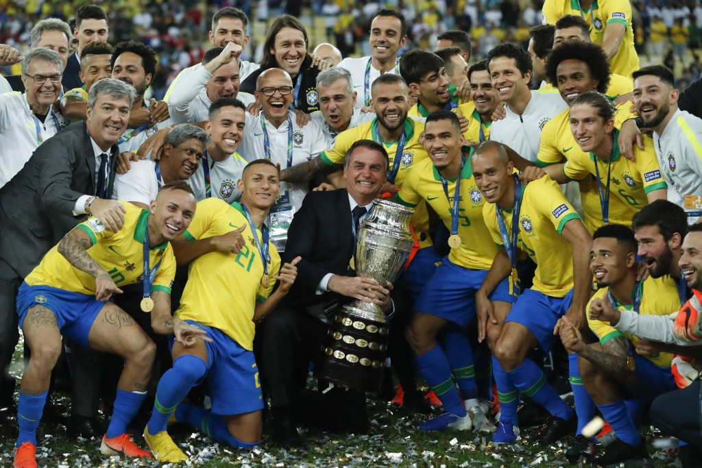 FILE - In this July 7, 2019 file photo, Brazil's President Jair Bolsonaro holds the Copa America trophy as he celebrates with Brazil's players after t...
