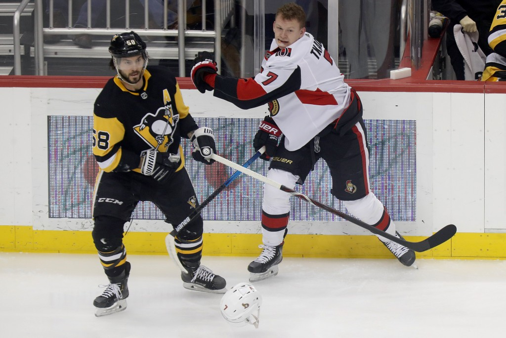 Ottawa Senators' Brady Tkachuk (7) has his helmet knocked off after a check by Pittsburgh Penguins' Kris Letang (58) during the first period of an NHL...