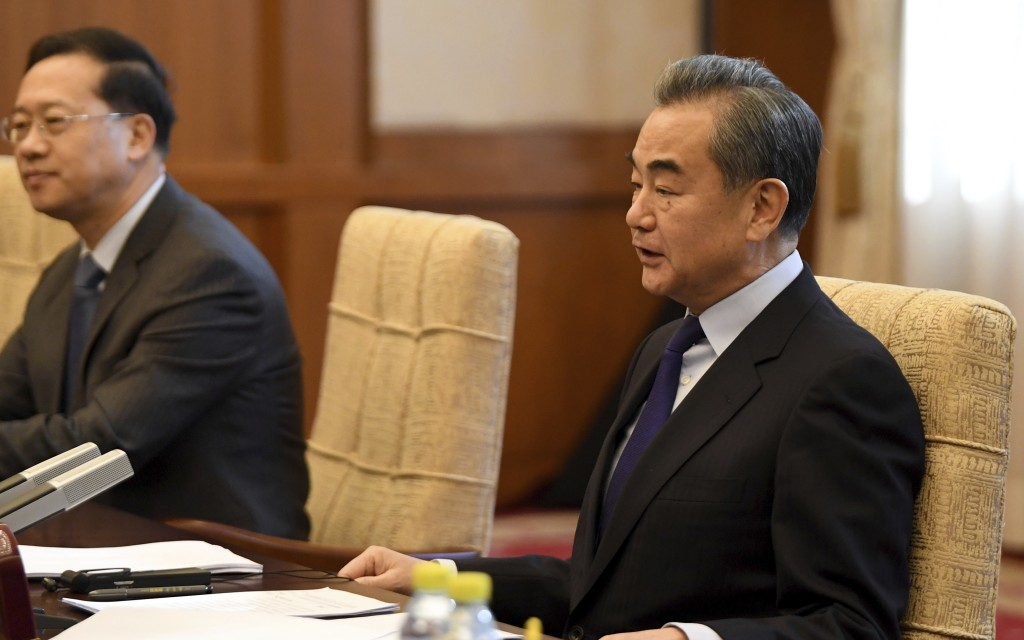 China's Foreign Minister Wang Yi talks to Iran's Foreign Minister Mohammad Javad Zarif during a meeting at the Diaoyutai state guest house in Beijing,...