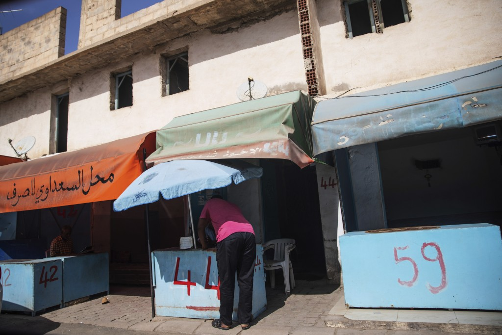 In this Tuesday, Sept. 24, 2019 photo, informal exchange offices line a street on a border town of Ben Garden, southern Tunisia. Tunisia is where the ...