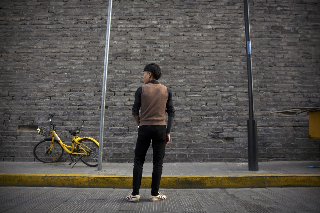 In this March 28, 2019, photo, Tylox user Yin Hao, who also goes by Yin Qiang, pauses while walking along a street near the old city walls in Xi'an, n...