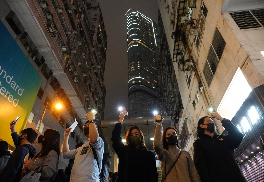 People raise their cellphones lights as they form a human chain on New Year's eve in Hong Kong, Tuesday, Dec. 31, 2019. Months of pro-democracy protes...