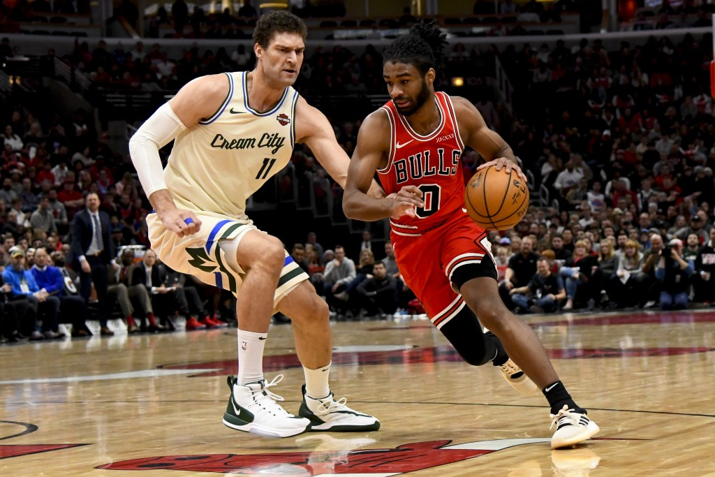 Chicago Bulls guard Coby White (0) dribbles past Milwaukee Bucks center Brook Lopez (11) during the first half of an NBA basketball game, Monday, Dec....