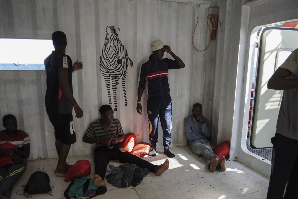 In this Sept. 8, 2019 photo, migrants rescued at sea by the NGOs SOS Mediterranée and Doctors Without Borders rest in the men's shelter aboard the Oce...