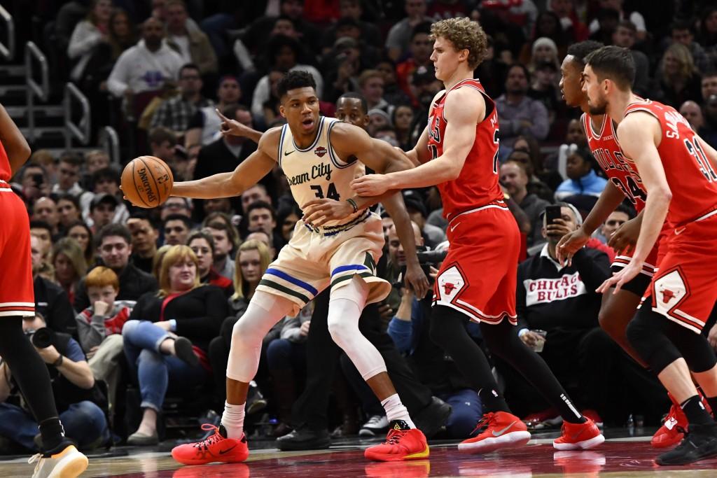 Milwaukee Bucks forward Giannis Antetokounmpo (34) dribbles away from Chicago Bulls forward Lauri Markkanen (24), center Wendell Carter Jr. (34) and g...