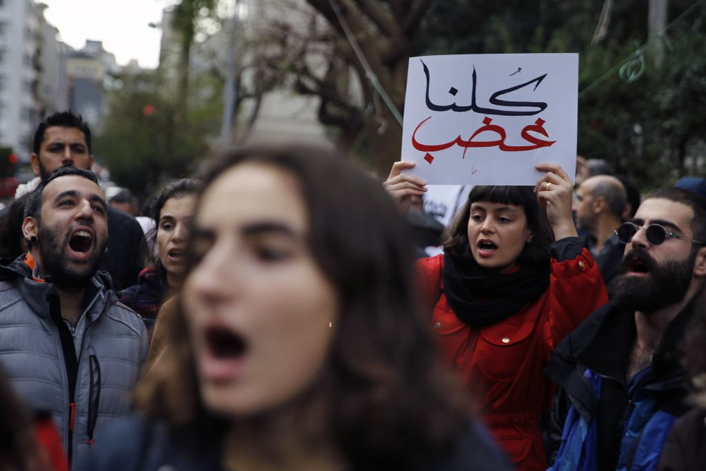 "Protesters chant slogans as one holds a placard with Arabic that reads, ""We are all outraged,"" during ongoing protests against the Lebanese political ..."