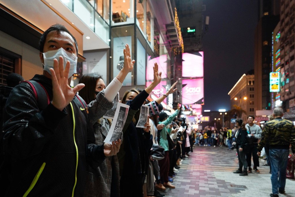 """People gesture to show """"five demands"""" as they form a human chain on New Year's eve in Hong Kong, Tuesday, Dec. 31, 2019. Months of pro-democracy prote..."""