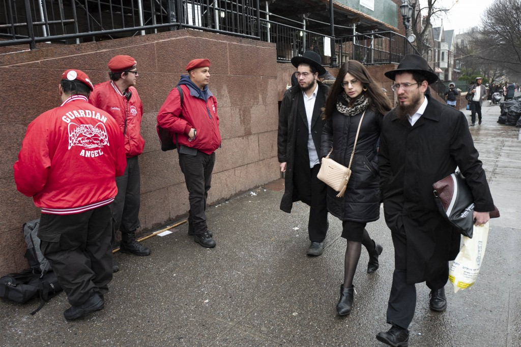 Members of the Guardian Angels, left, a volunteer safety patrol organization, stand in front of the Chabad Lubavitch World Headquarters, Monday, Dec. ...