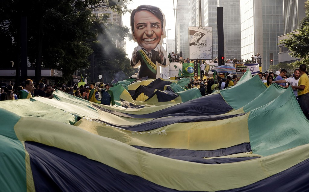 FILE - In this May 26, 2019 file photo, supporters of Brazil's President Jair Bolsonaro feature a large, inflatable doll in his image as they demonstr...