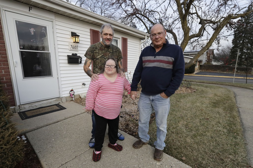 In this Friday, Dec. 20, 2019 photo, Tyrone Cefalu, right, Bobby Goldberg, left, and his sister Debbie Goldberg pose for a photo in front of Bobby Gol...