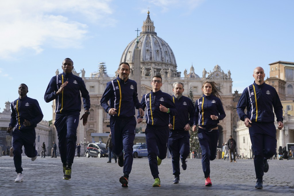 FILE - In this Jan. 10, 2019, file photo, members of the Vatican Athletics sports team run for the media in front of St. Peter's basilica, at the Vati...