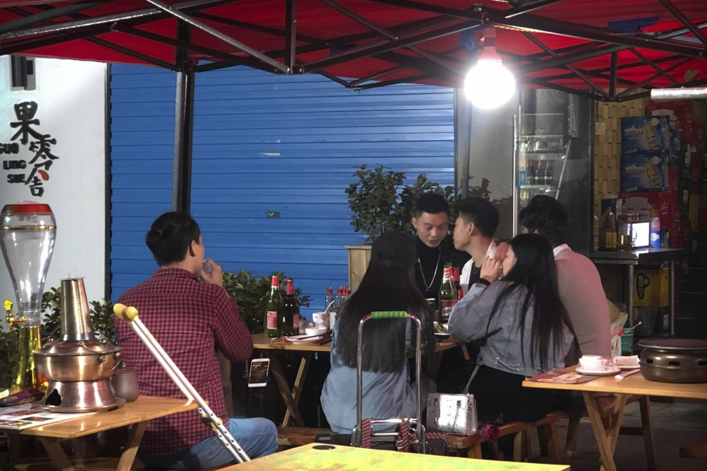 In this Dec. 6, 2019 photo, Wu Yi, who has struggled with Oxycontin abuse, sings a song for customers at an all-night restaurant in Shenzhen in southe...