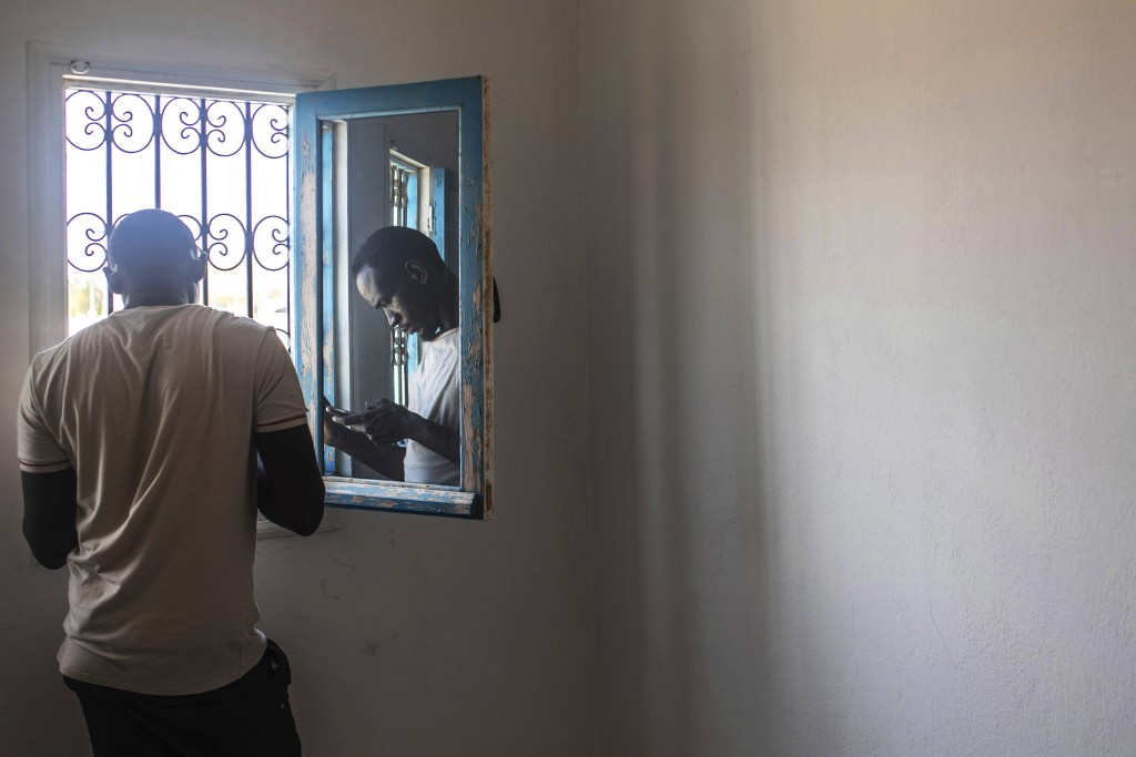 In this Monday, Sept. 23, 2019 photo, Abdullah, 25, a Sudanese migrant who tried crossing the Mediterranean from Libya, is reflected in a window as he...