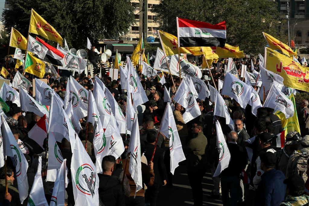 Iran-backed Popular Mobilization Forces gather outside the heavily fortified Green Zone, the seat of Iraq's government and the U.S. embassy, in Baghda...