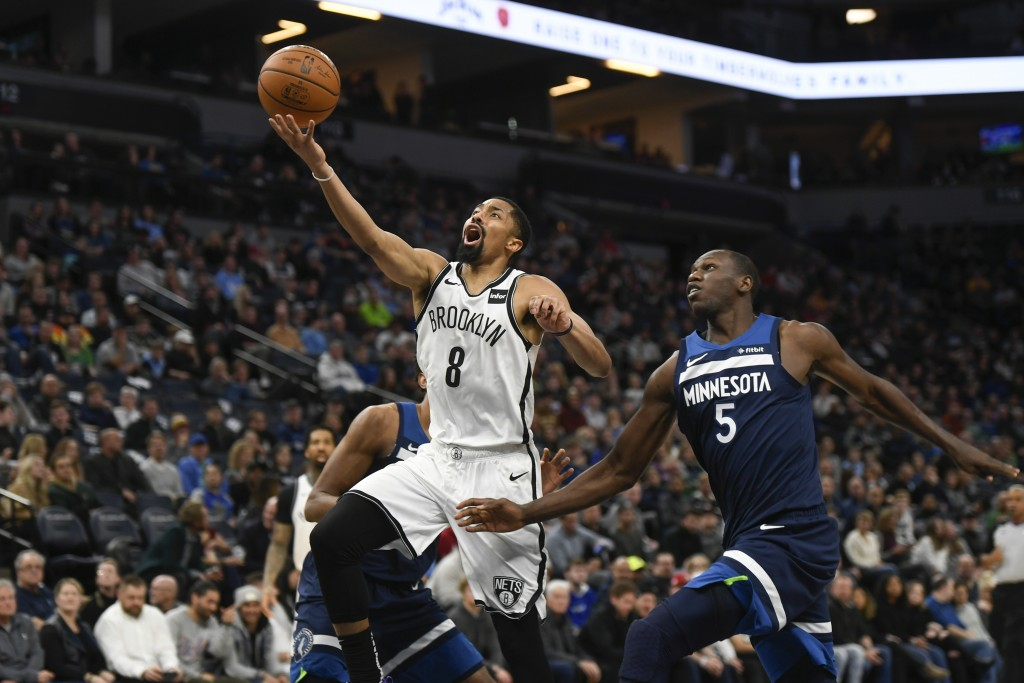 Brooklyn Nets guard Spencer Dinwiddie (8) goes up for a layup past Minnesota Timberwolves center Gorgui Dieng during the first half of an NBA basketba...