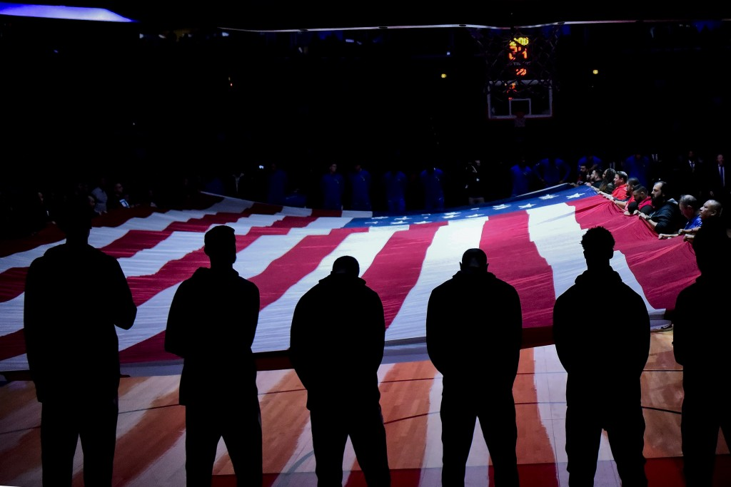 A United States flag is displayed as the national anthem is sung before an NBA basketball game between the Chicago Bulls and the Milwaukee Bucks, Mond...