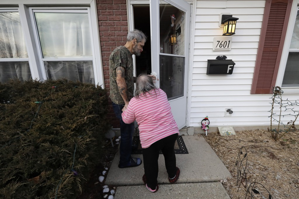 In this Friday, Dec. 20, 2019 photo, Bobby Goldberg, left, and his sister Debbie enter their home in suburban Chicago. Goldberg has filed a lawsuit cl...