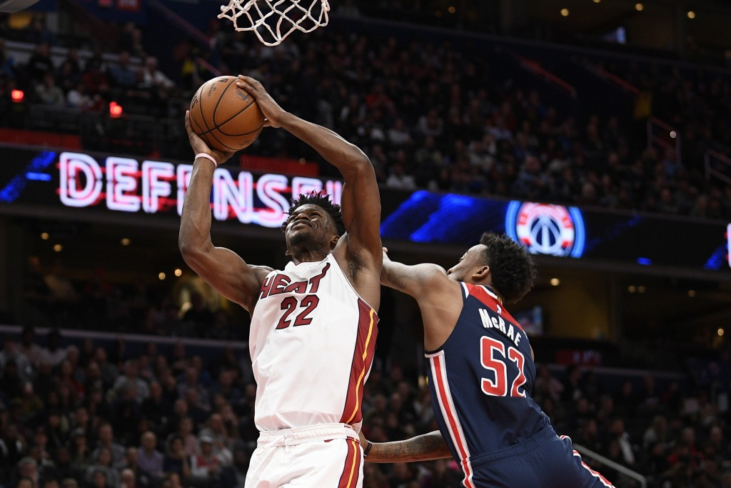 Miami Heat forward Jimmy Butler (22) goes to the basket past Washington Wizards guard Jordan McRae (52) during the first half of an NBA basketball gam...