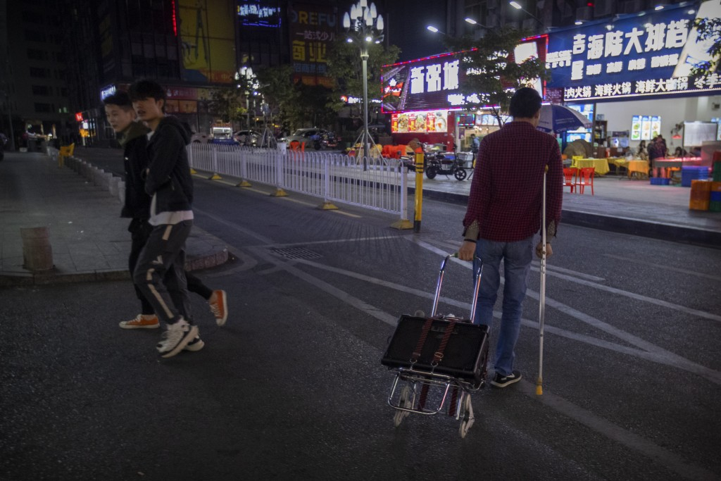 In this Dec. 6, 2019, photo, Wu Yi, who has struggled with Oxycontin abuse, crosses a street while on his way to sing songs for money at all night-res...