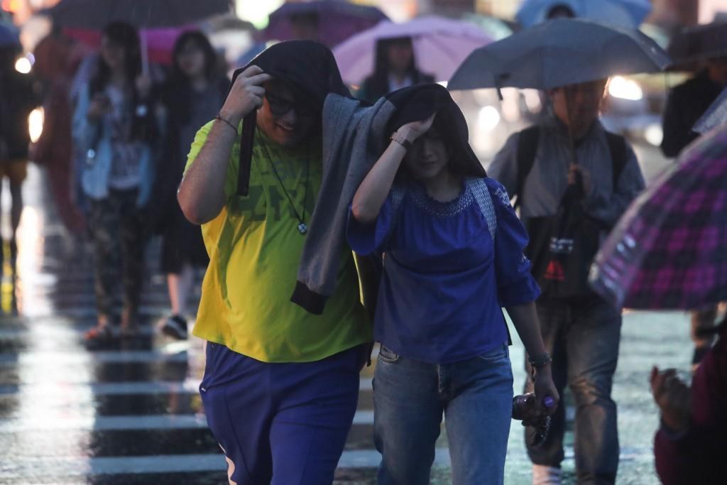 未攜帶雨具的民眾用衣物遮雨
