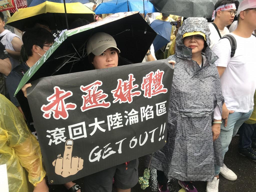 「拒絕紅色媒體、守護台灣民主」活動23日在凱達格蘭 大道舉行,參與民眾舉標語表達訴求。 中央社記者徐肇昌攝 108年6月23日