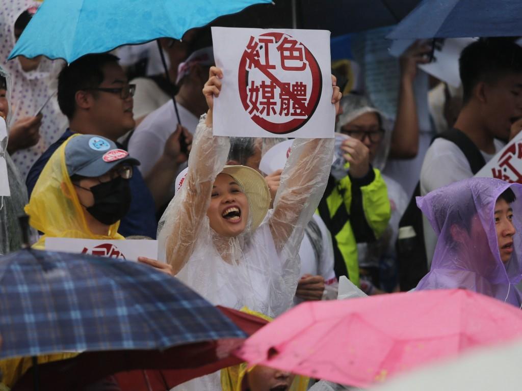 「拒絕紅色媒體、守護台灣民主」活動23日下午在凱達 格蘭大道登場,許多民眾穿雨衣、撐傘到場參與,有人 舉出反紅色媒體標語。 中央社記