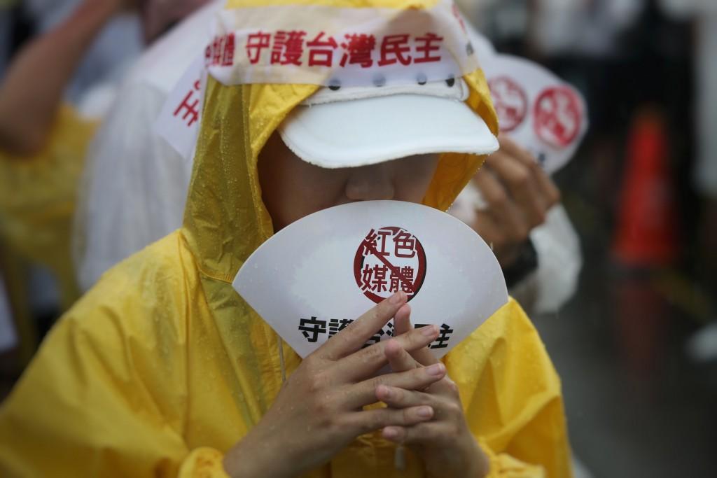 「拒絕紅色媒體、守護台灣民主」活動23日下午在總統 府前凱達格蘭大道舉行,許多民眾不畏雨勢到場參與, 手持標語表達立場。 中央社記者