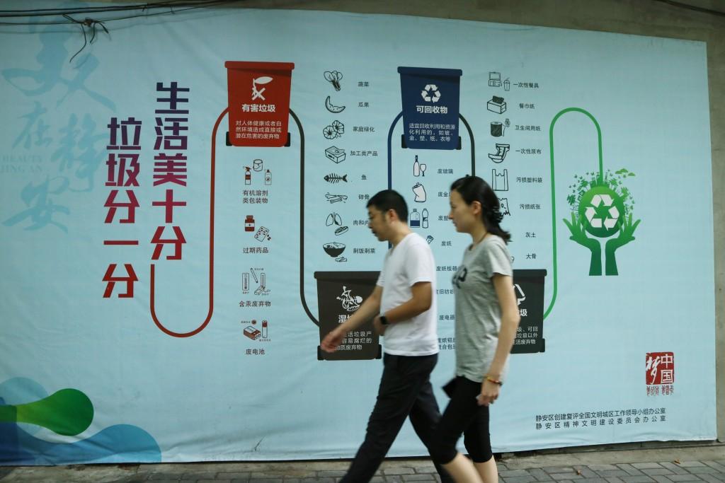 上海民眾走過宣導垃圾分類的民宅外牆
