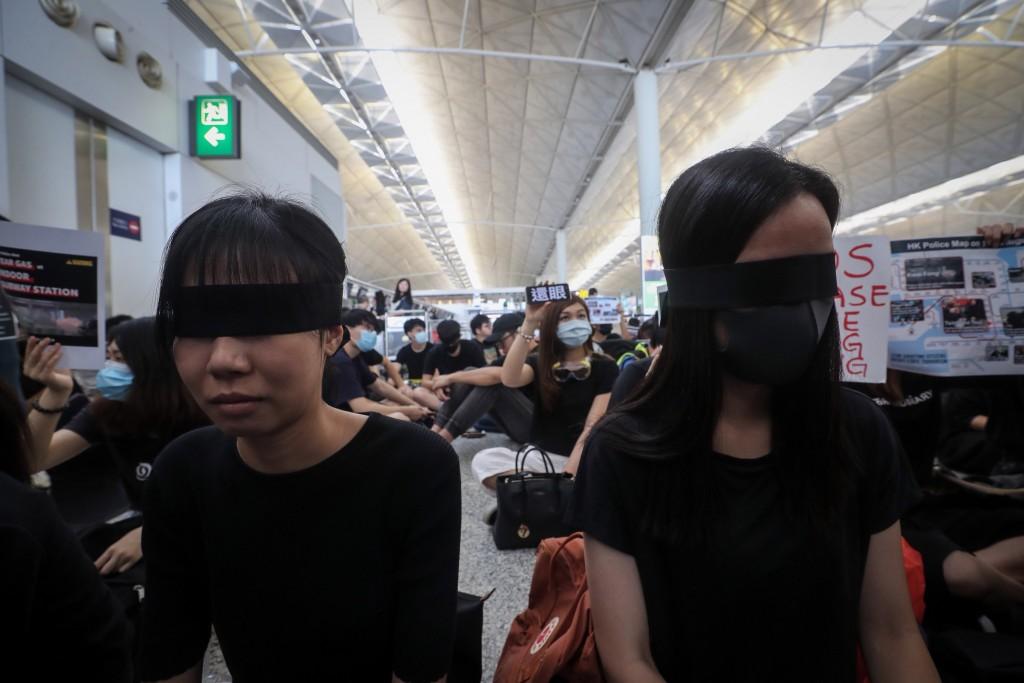 香港「反送中」抗爭11日遭警方空前強勢鎮壓,一名示 威女子遭射傷右眼,引發黑衫軍強烈憤慨,12日中午1 時號召全民罷工,民眾以黑布遮眼...