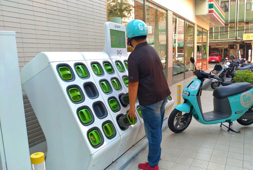 Gogoro rider swaps batteries at battery charging station