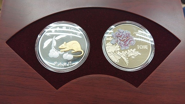 Central bank chooses golden rat, pink drunken hibisicus for its latest commemorative coin sets.