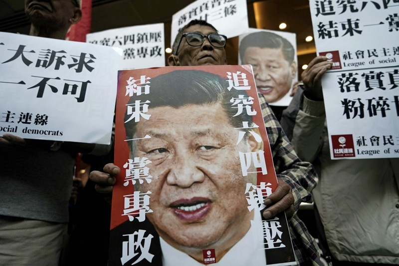 Pro-democracy activists hold up placards of Chinese President Xi Jinping at a ferry terminal in Hong Kong.