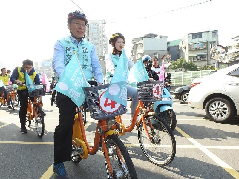 台灣民眾黨主席柯文哲(前左)6日到新北市三重區為黨籍立委候選人李旻蔚助選,以騎單車方式掃街拜票。中央社