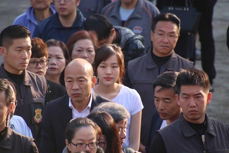國民黨總統候選人韓國瑜(前)跟女兒韓冰(後方白衣者),一早就前往投票所,在隊伍中等待領票。中央社