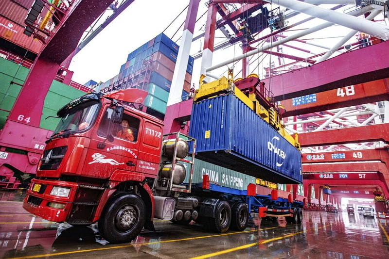 A worker waits to transport containers at the container port in Qingdao in eastern China's Shandong.