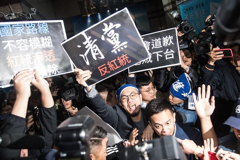 數名青年黨員15日在國民黨中央黨部大廳高舉「清黨 反紅統」看板抗議,與黨工、保全發生衝突。中央社