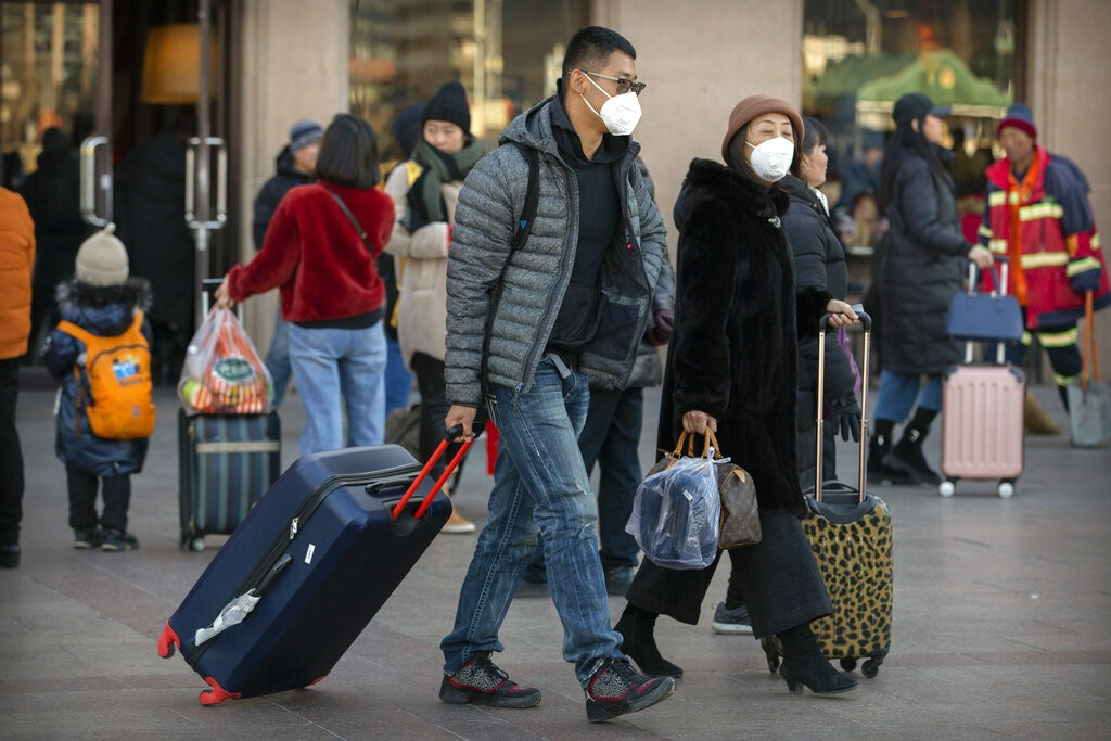 Travelers wear face masks outside Beijing Railway Station, China.