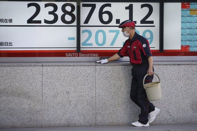 A worker cleans up an electronic stock board of a securities firm in Tokyo.