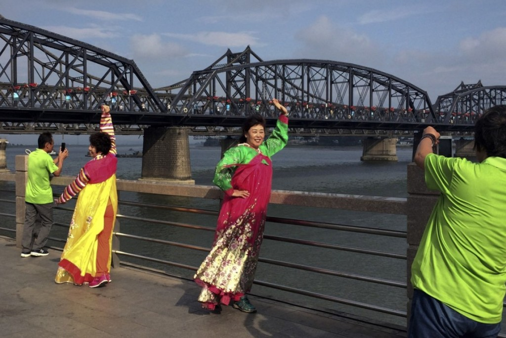 Chinese tourists in North Korean costumes pose for photos.