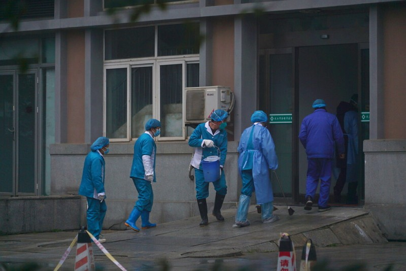 Hospital staff wash the emergency entrance of Wuhan Medical Treatment Center.