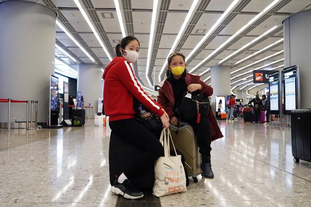 香港民眾在車站外戴口罩防病毒。(美聯社圖片)