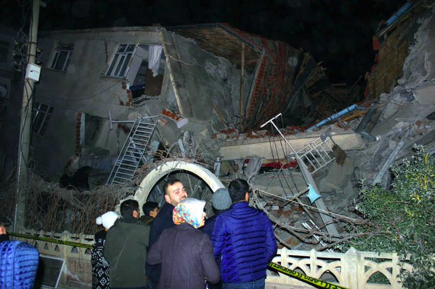 People look at a collapsed building after a 6.8 earthquake struck Elazig city center in eastern Turkey, Friday, Jan. 24, 2020. An earthquake with a pr...
